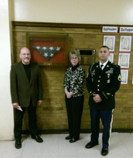 An adult man and woman and a uniformed soldier stand in front of the flag case in a school hallway