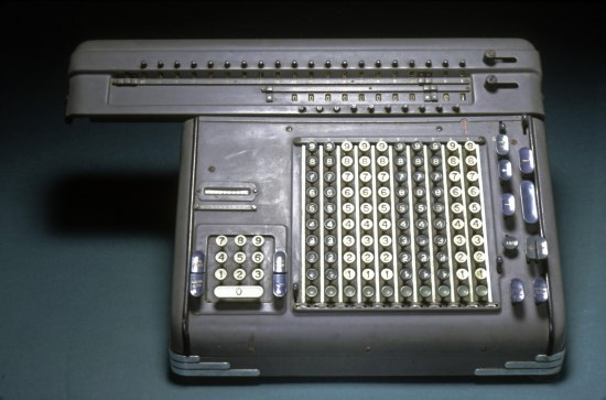 A grey metal device that looks sort of like a typewriter. There are not letters but numbers on the keys and they are different colors.