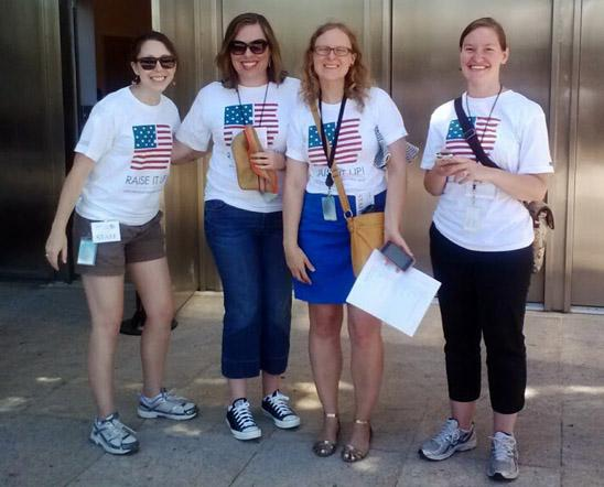 Three staff members and one intern pose for a photo during the Raise It Up program, wearing matching US flag shirts