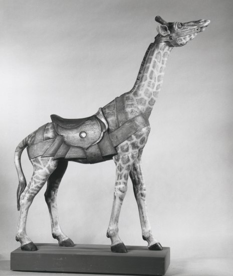 Black and white photo of a giraffe carousel figure with long neck and saddle