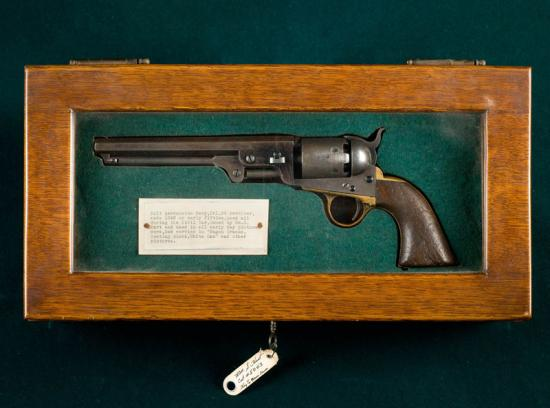Gun in wooden frame with paper label