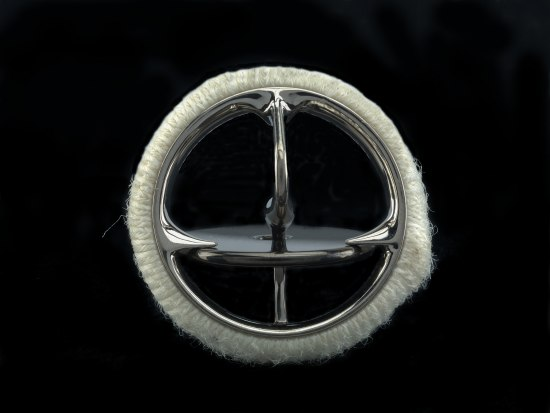 A circular band covered in a white knit fabric that looks like cotton. There is a metal component creating a second ring with a disc in the middle, connected on the top and bottom by metal pieces and resting on two pieces of the silver metal that jut out from the ring. The center portion looks like it could be a child toy top.