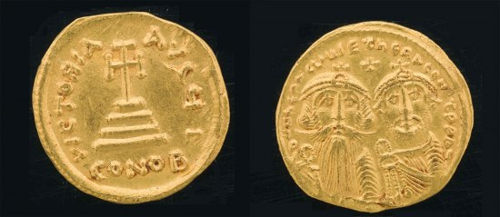 A coin with two bearded men on it along with text and a small cross. On the obverse side, there is an image on a cross on some steps with writing around the edges