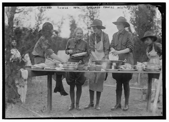 Five women in uniforms (with pants and aprons) stand at an outdoor table, washing dishes in a line.