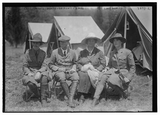 Black and white photo of four people sitting in front of canvas camp tents: three women, one man. They wear military-style uniforms and boots. All are wearing hats. One woman holds a trumpet/bugle.
