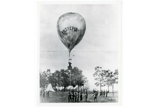Illustration of a balloon with the name INTREPID on it and people watching it go up.