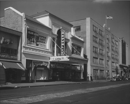 Black-and-white photo of a theater and surrounding buildings