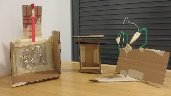 Objects created out of cardboard, pipe cleaners, masking tape, brads and straws.