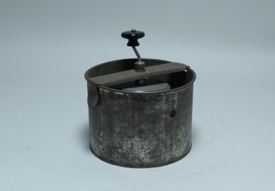 A black metal pot which looks scuffed up with a crank attached to the top.