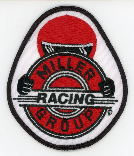 An iron-on patch. There is a motorist in a red and back helmet appearing to drive right at the viewer. It saying Miller Racing Group on his steering wheel.