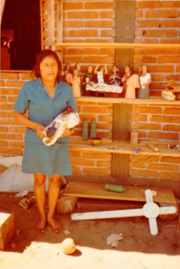 An faded photograh of a woman standing barefoot outdoors  by a brick building holding an object. There are shelves behind her with figurines