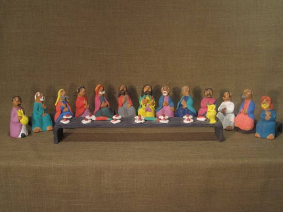 A line of figurines that look like men seated wearing long, colorful robes behind a long table with white plates on it.