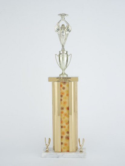 A trophy.  There is a silver figure on top holding something aloft but the rest of the trophy is gold with a center stripe having daisy-like accents