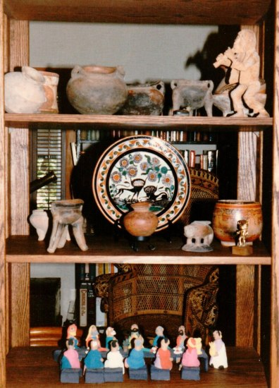 A photograph using a bright flash of an interior of a home; the photograph is set up in front of three shelves that hold ceramic or earthen objects, including plates, bowls, and figurines.
