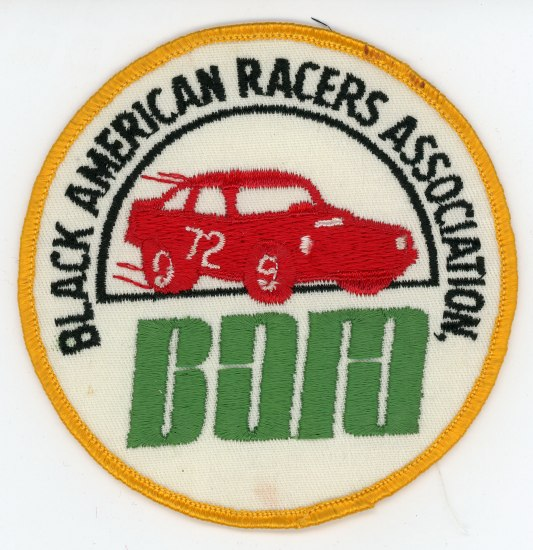 An iron on patch. It is white with a yellow outline and a red car zooming through some text in the middle