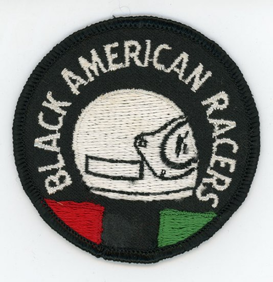 A black iron on patch with a white helmet on the front