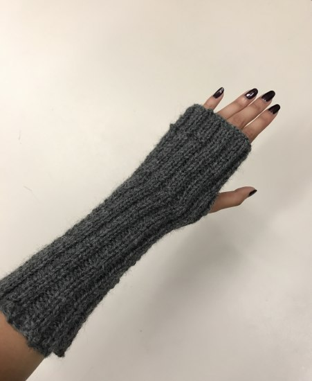 Photo of an arm and hand wearing a wristlet. It's like a long mitten but fingers and thumb emerge.