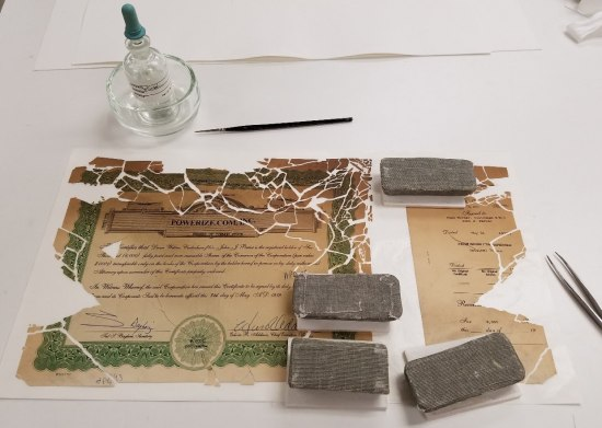 On a white surface a burnt piece of paper lies in pieces. There are several gray rectangular objects laid on different parts of the paper. Tweezers lie to one side and a clear bottle with a dropper sits by the top.