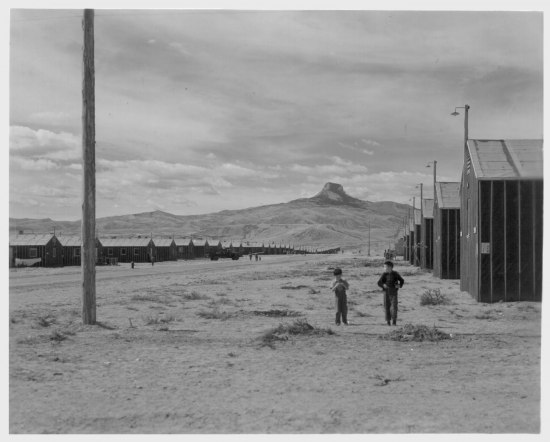 Black and white photograph of desolate scene with cabins/buildings on right, boys walking, and a mountain in the distance.