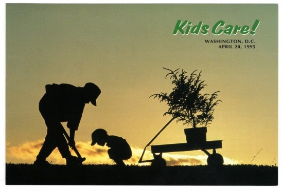 Photo with rising sun. In silhouettes, two children dig a hole to plant a tree. The small tree is in their Little Red Wagon. They wear baseball hats.