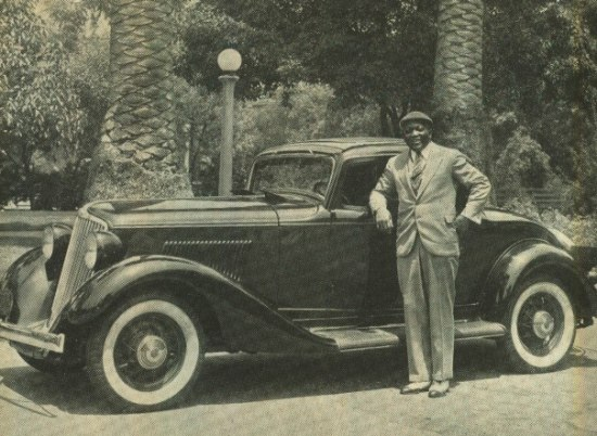 Black and white photograph of a man in a light-colored suit and cap standing in front of a gleaming black car outside with palm trees in the background.