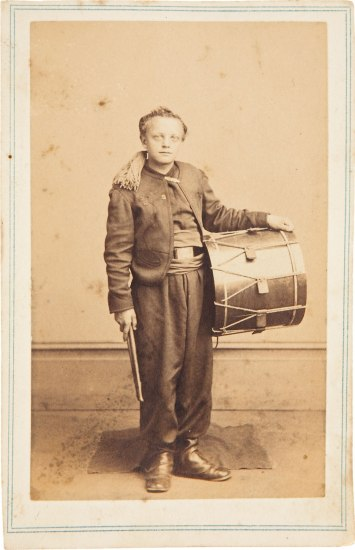 A faded photograph of a boy in dark pants and a jacket. He holds a drum at his side and a pair of drumsticks in his other hand