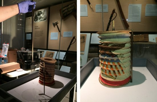 Two photos juxtaposed of a lantern that looks like an accordion sitting propped up on a white base in a museum exhibit. In one photo a person wearing a purple glove holds a metal rod up which seems to be connected with a glass disco and another rod.
