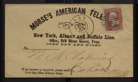 "an envelope that reads ""Morse's American Tele"" from an office in Troy, NY. The paper is faded and has cursive writing on it."