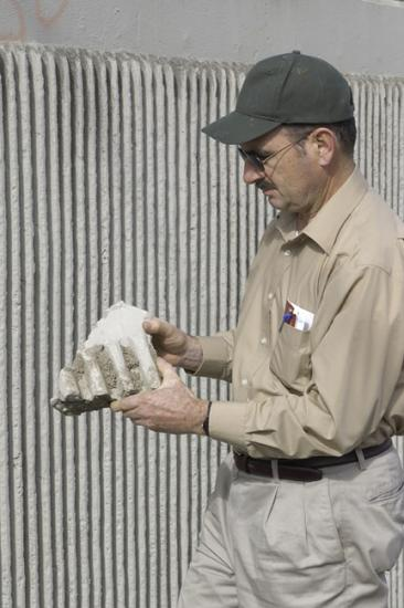 Man in baseball cap holding a baseball glove-sized chunk of concrete