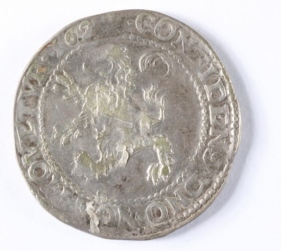 A silver-colored coin with uneven edges. It is not shiny but shows signs of wear. There is a lion on its hind legs within a circle. Text runs around the outside of the coin.