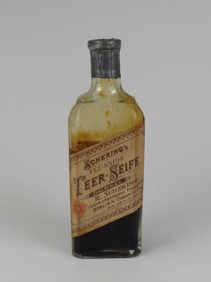 "A bottle with a label. The label is yellowed with age and and has writing on it. The words ""pharmaceut"" and ""Berlin"" are evident. Inside the bottle is a brown liquid."