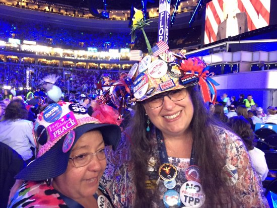 Two women smile for the camera, wearing hats covered in buttons. Behind them, a full convention hall bathed in blue lights.