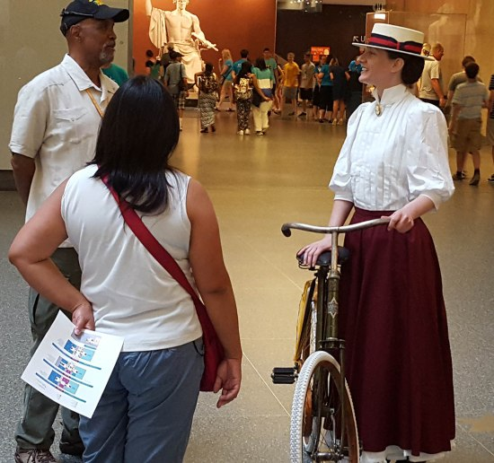 Photo of woman dressed in 1890s clothing with a bicycle, talking to museum visitors