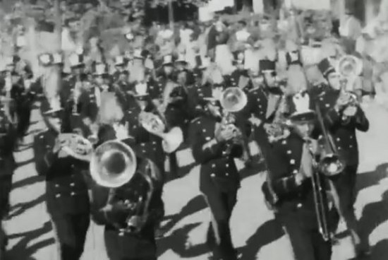 Black and white still from a movie. A marching band is playing their instruments in formation, marching along. They have fancy hats.