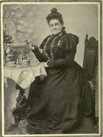 A black and white photograph of a woman in a black dress with a corset, puffy sleeves and a full skirt sitting at a small table on which is a tea set. The woman is holding something in her right hand and looking directly at the camera.