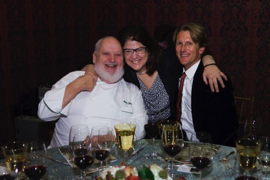 Color photo. Three people at a dining table with white tablecloth embrace and smile for the camera. On the table, glasses of wine.