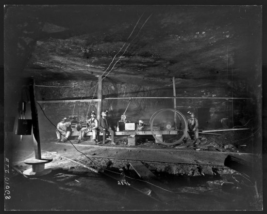 Black and white photo of miners in a mine sitting on a wooden bench
