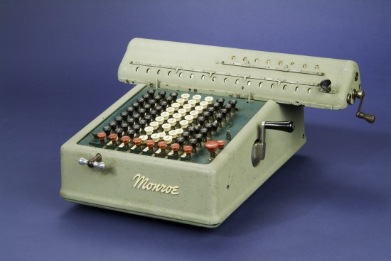 A mint green metal device that looks like a cross between a typewriter and a telephone. There are two small handcranks on it and a number of keys on the surface.