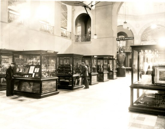 A black and white photograph of a large gallery with rows of glass display cases. Several men look into them to look at the artifacts inside.