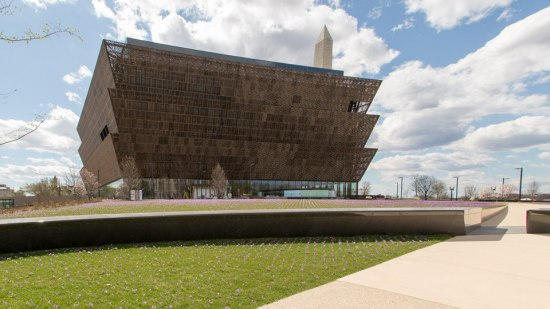 an exterior shot of the National Museum of African-American History and Culture on a sunny day with a blue sky with clouds. The photo is taken far away from the building so you can see sidewalks, grass and a short wall. The building has three levels of metal walls that are stacked on each other.