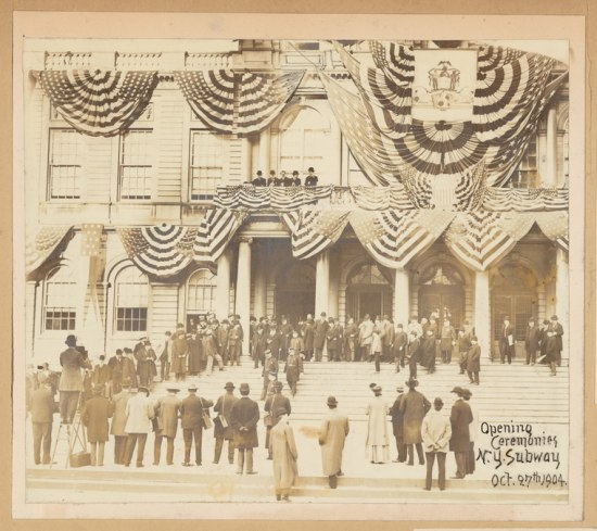 Men in coats and hats stand on the steps of City Hall. Above bunting seems to drip off every flat surface.