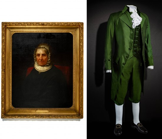 A painting in a gold frame of a woman with a neck ruff and a ruffled cap and a photo of an old-fashioned, shiny green suit with white socks, black shoes with buckles, and ruffles at the neck and sleeves.