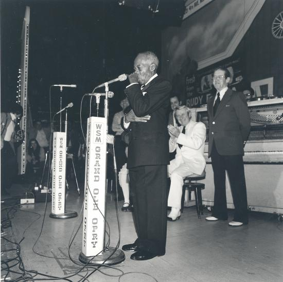 "Man in suit on stage playing harmonica, with tangle of microphone cords on floor. Microphone says ""WSM GRAND OLE OPRY"" on it."