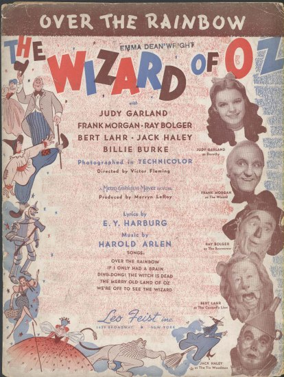 "The cover of sheet music for ""Somewhere Over the Rainbow."" The  main characters faces are on the right side and there's a red, white and blue color scheme. There are other illustrations from the film around the edges and in the center are credits for the work."