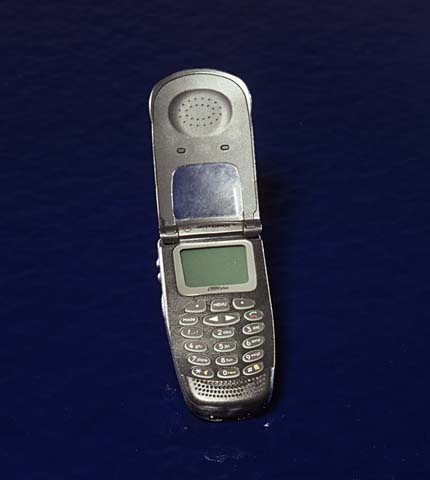 A battered-looking granite-colored flip-up cell phone laying open