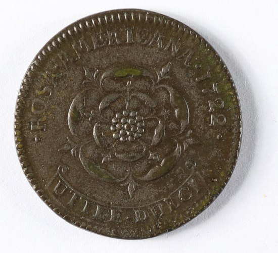 A deep bronze or copper colored coin. In the center is a flower with several rings of petals open. The edges are slightly serrated and there is text above and below the coin.