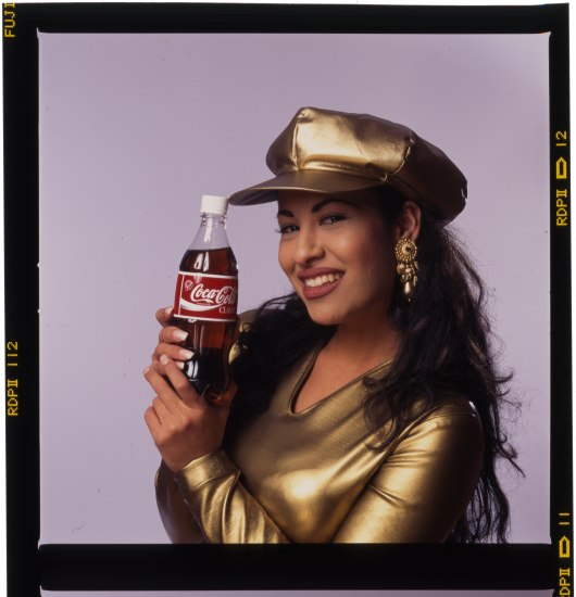 A dark-haired woman in a gold hat and top holds up a bottle of Coca Cola and smiles. There is a dark border created by the visible film strip around the photograph.