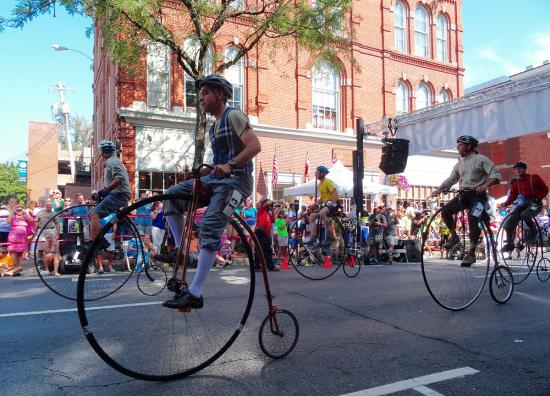 Side view of a rider on a high wheel bicycle