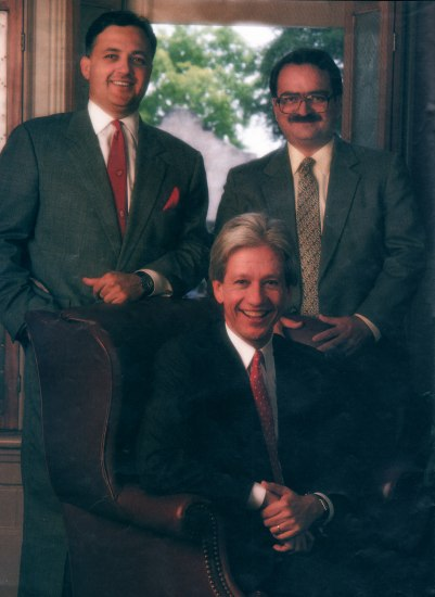 Two men stand and one sits in this formal portrait. All three wear suits and ties.