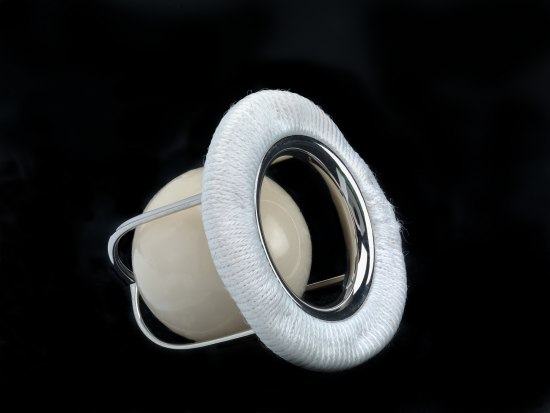 A contraption made of silver metal, a ball that looks like a beige marble, and some white cloth or fabric wrapped around a ring. The ball sits inside of a cup made from several metal pieces extending from the fabric and metal ring.